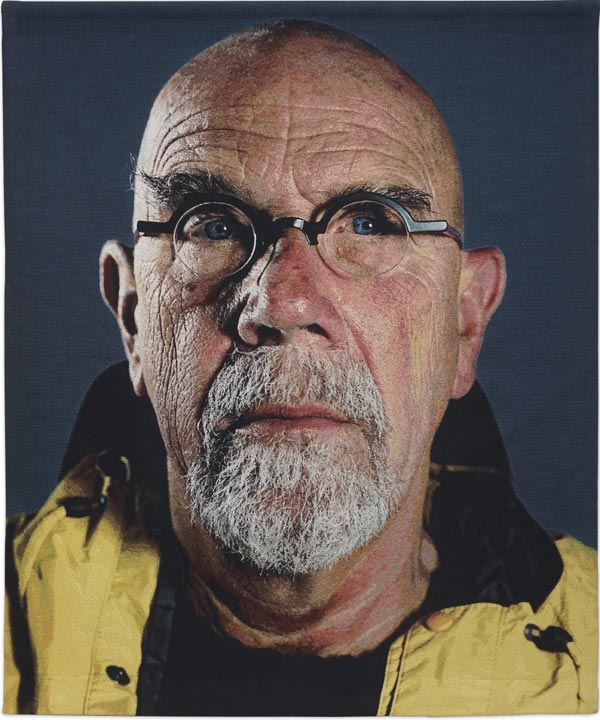 Chuck Close,  Self-Portrait (Yellow Raincoat), 2013, Jacquard tapestry, 93 x 76 in., Private Collection, © Chuck Close in association with Magnolia Editions, Photograph Courtesy Artist and Pace Gallery