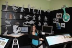 """Blue Sky Studios animator Alena Wooten hangs out in a simulation of her digital sculpting workspace, as seen in the exhibition """"'Ice Age' to the Digital Age."""" (Photo ©Norman Rockwell Museum. All rights reserved.)"""