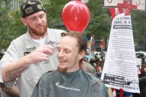 Matthew Ketchum gives a MorganChase 'banker' a haircut at Zuccotti Park
